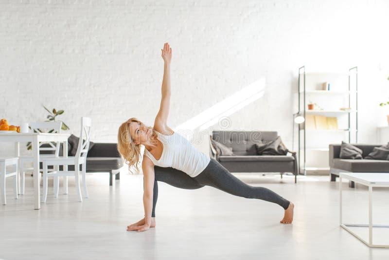 Donna di Yuong che si siede sul pavimento nella posa di yoga fotografia stock