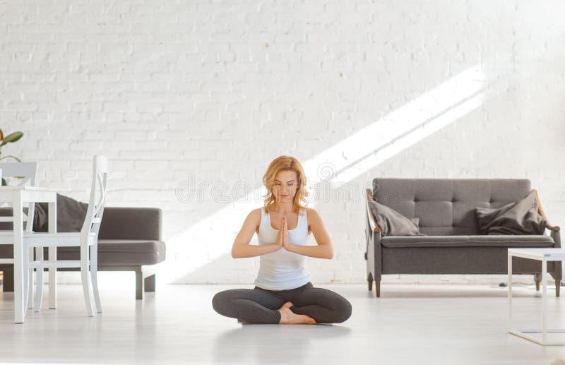 Donna di Yuong che si siede sul pavimento nella posa di yoga fotografia stock libera da diritti