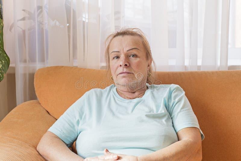 Donna diabolica che si siede sullo strato e che esamina la macchina fotografica immagine stock libera da diritti