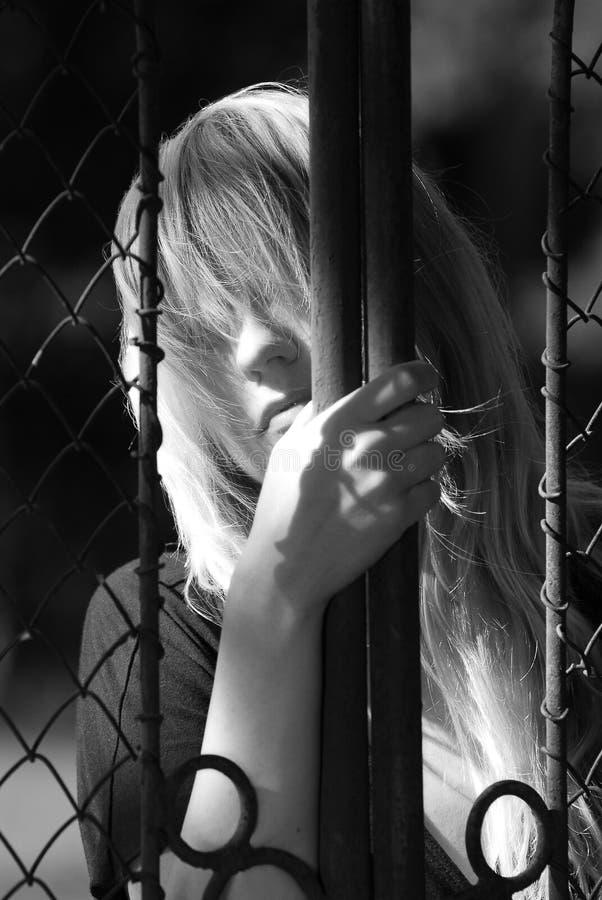 Donna dietro il cancello del metallo fotografie stock