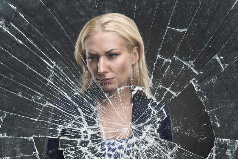 Donna dietro un vetro rotto immagine stock
