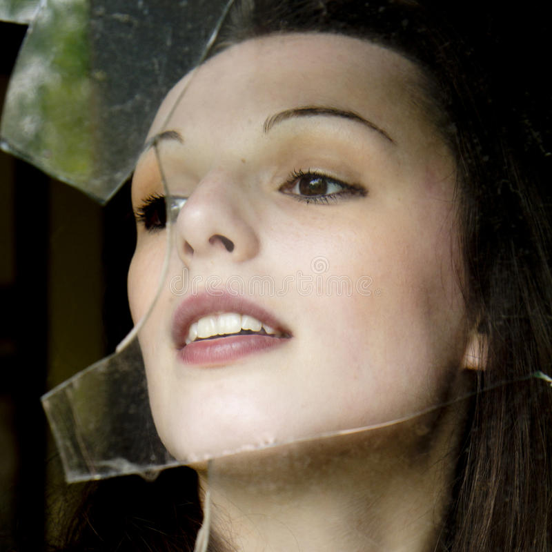 Donna dietro una finestra rotta. fotografia stock