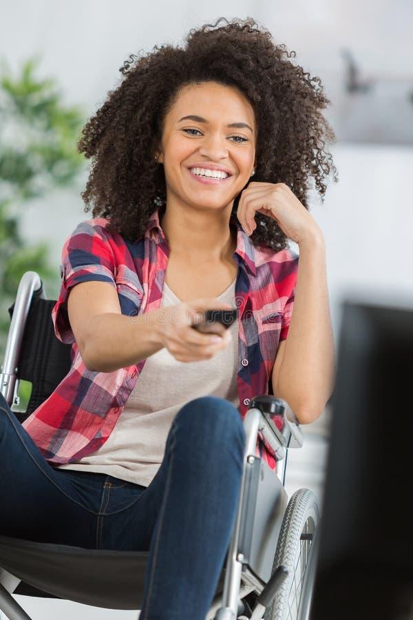 Donna disabile felice del ritratto che guarda TV a casa immagini stock libere da diritti