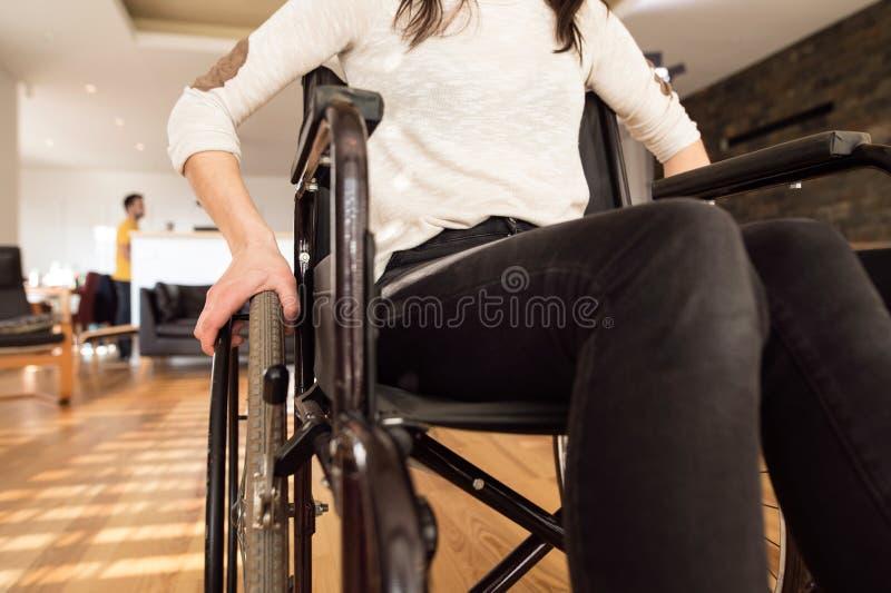 Donna disabile irriconoscibile in sedia a rotelle a casa in ro vivente fotografia stock libera da diritti