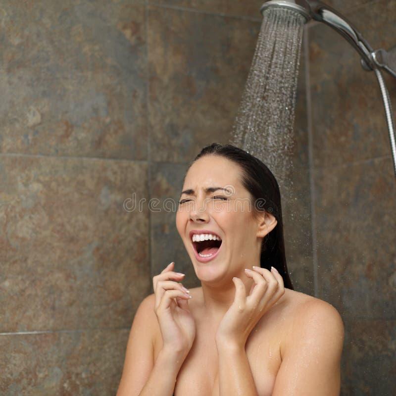 Donna disgustata che grida nella doccia sotto l'acqua fredda fotografia stock libera da diritti