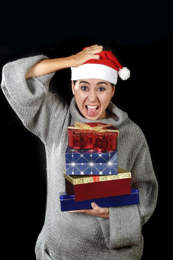 Donna disperata divertente in cappello di Santa Christmas nello sforzo circa i grida di compera dei regali e dei presente di dice fotografie stock libere da diritti