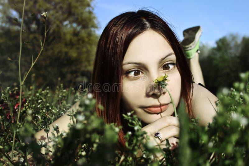 Donna divertente che odora un fiore fotografia stock