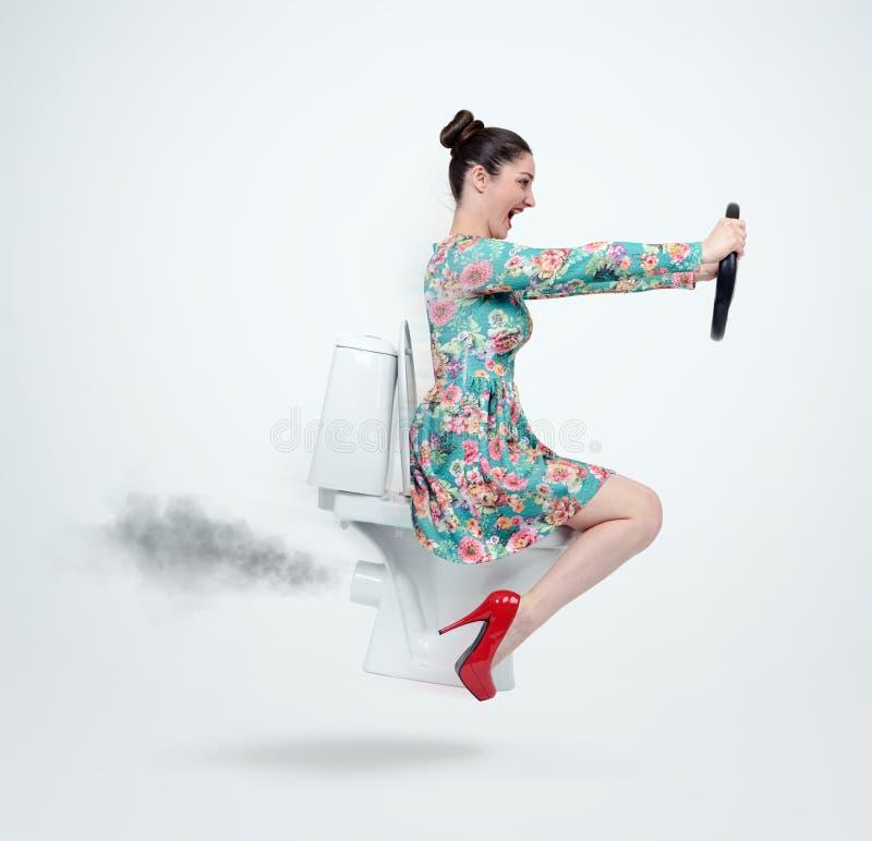 Donna divertente nel volo del vestito sulla toilette con il volante Concetto di movimento fotografia stock libera da diritti