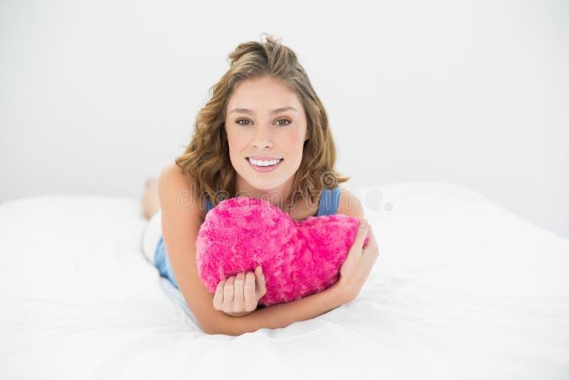 Donna dolce attraente che stringe a sé con il suo cuscino del cuore che sorride alla macchina fotografica fotografie stock libere da diritti