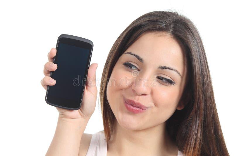 Donna dolce che mostra uno schermo nero del telefono cellulare immagini stock