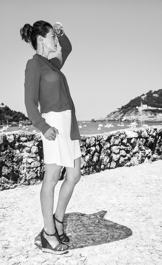 Donna a Donostia; San Sebastian, Spagna che esamina distanza fotografie stock