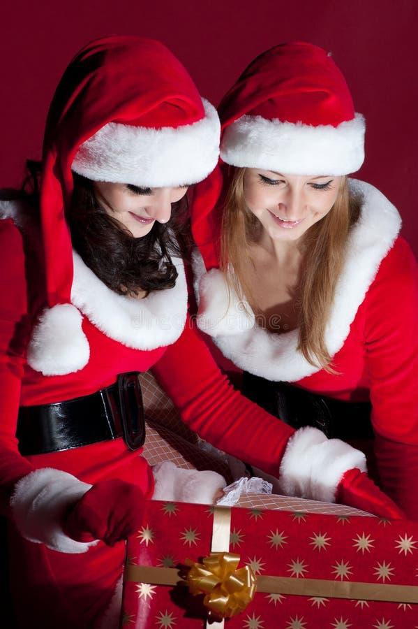 Donna due in regalo di natale di apertura del costume della Santa. immagini stock