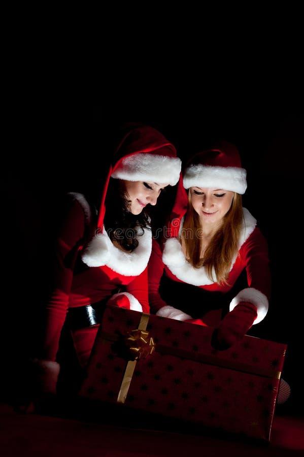 Donna due in regalo di natale di apertura del costume della Santa. fotografia stock