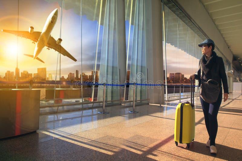 Donna e bagagli di viaggio che camminano in terminale ed aria di aeroporto fotografia stock