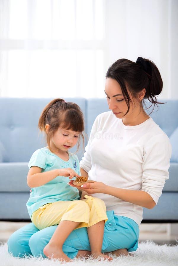 Donna e bambina che si siedono sul tappeto sul pavimento a casa La giovane conversazione della madre comunica con la piccola figl fotografia stock