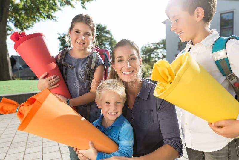 Donna e bambini al giorno di iscrizione con i coni della scuola fotografia stock libera da diritti