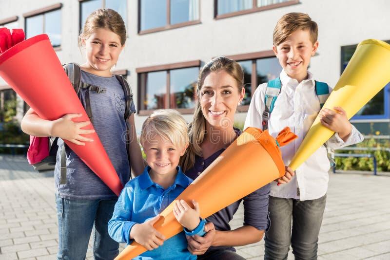Donna e bambini al giorno di iscrizione con i coni della scuola fotografia stock