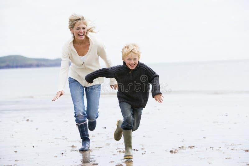Donna e bambino che funzionano sulla spiaggia immagine stock libera da diritti