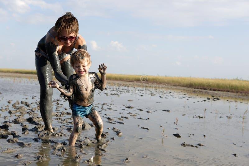 Donna e bambino in fango curativo fotografia stock libera da diritti