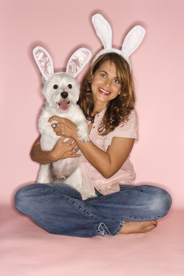 Donna e cane con le orecchie di coniglio fotografie stock libere da diritti