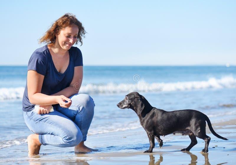 Donna e cane sulla spiaggia immagini stock libere da diritti
