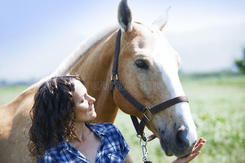 Donna e cavallo insieme fotografia stock