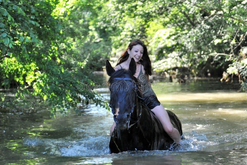 Donna e cavallo nel fiume fotografia stock libera da diritti