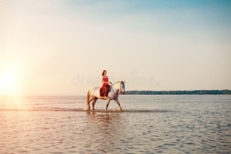Donna e cavallo sui precedenti del cielo e dell'acqua Ragazza o di modello fotografia stock