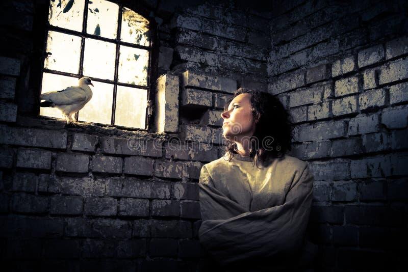 Donna e colomba di bianco in prigione come simbolo dei sogni di libertà fotografia stock libera da diritti