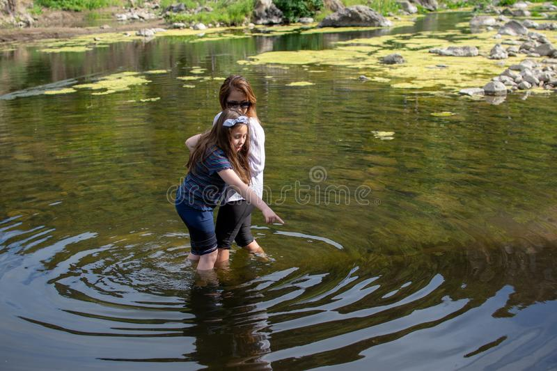 Donna e figlia che attraversano con attenzione in una corrente o in un fiume fotografia stock