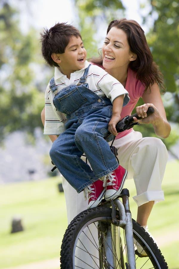 Donna e giovane ragazzo su una bici all'aperto che sorridono fotografia stock