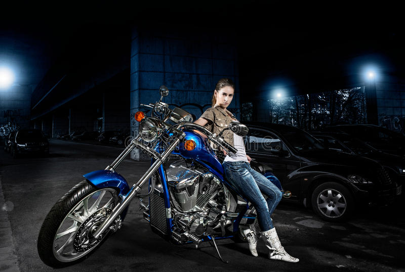 Donna e la sua motocicletta all'aperto alla notte fotografia stock libera da diritti