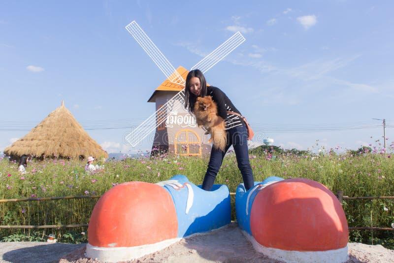 Donna e pomeranian tailandesi con le grandi scarpe nel giacimento dell'universo, Muangkaen fotografia stock