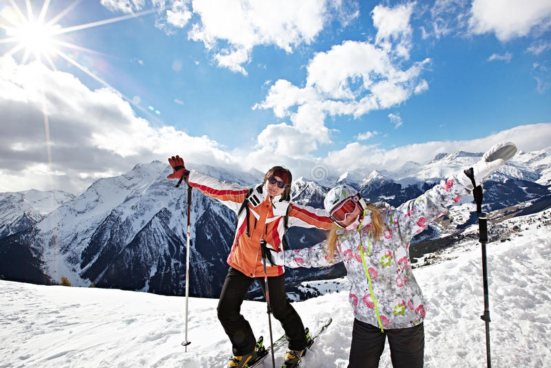 Donna e ragazza felici sulla stazione sciistica delle montagne immagini stock