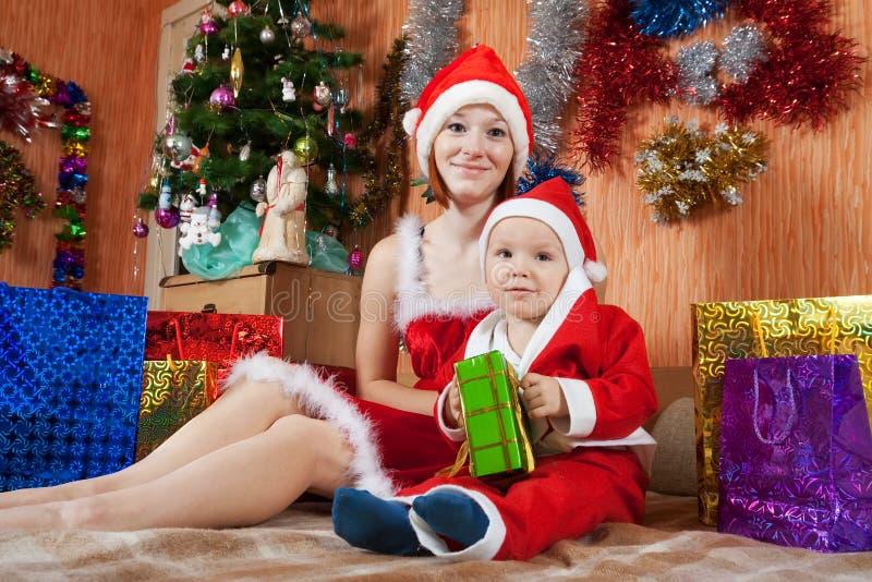 Donna e ragazzo vestiti come il Babbo Natale fotografia stock libera da diritti