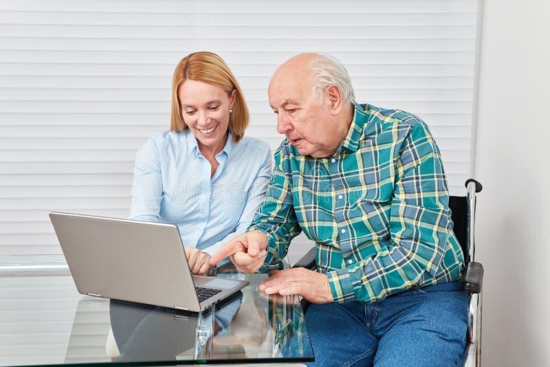 Donna ed anziano curioso con il computer della compressa fotografia stock