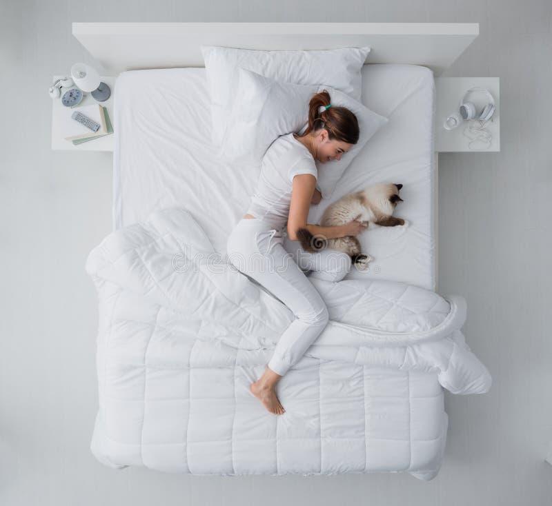 Donna ed il suo gatto nella camera da letto fotografia stock libera da diritti