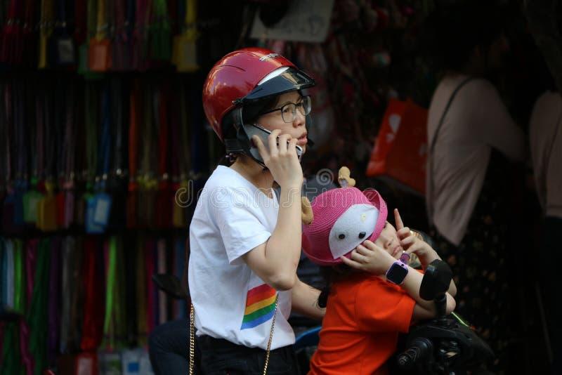 Donna ed il suo motociclo di arresto e del parco della figlia per il telefono alla città di commercio di Sampheng fotografie stock