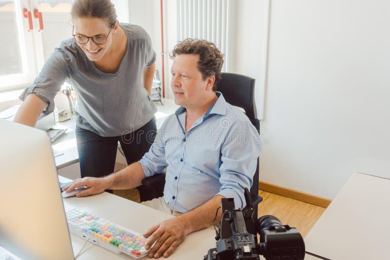 Donna ed uomo che lavorano ad un video nella post produzione immagini stock libere da diritti