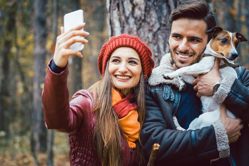 Donna ed uomo con il loro cane sulla passeggiata di autunno che prende un selfie del telefono fotografia stock
