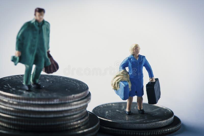 Donna ed uomo miniatura sui mucchi delle monete del dollaro fotografia stock