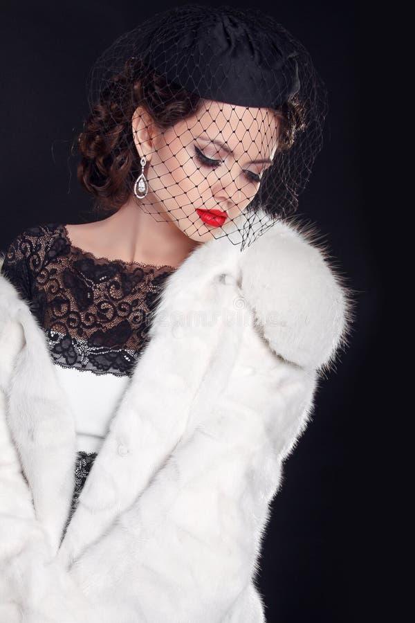 Donna elegante che indossa in pelliccia bianca isolata su backgr nero fotografie stock libere da diritti