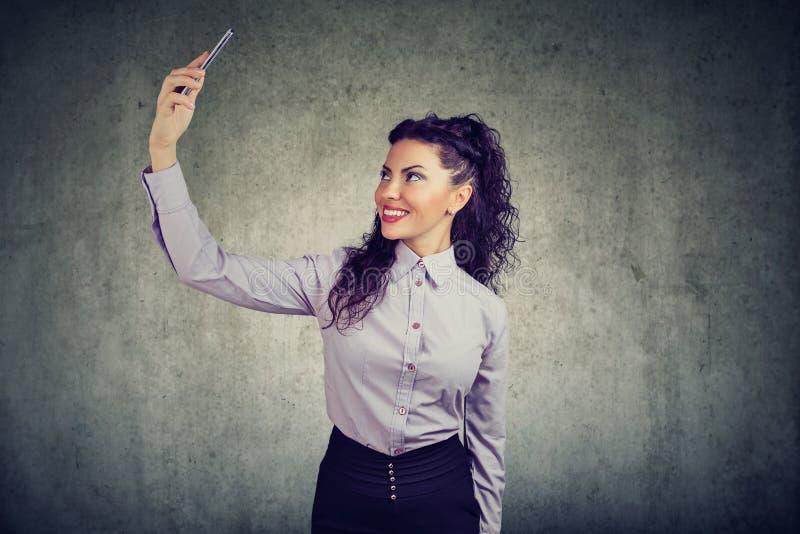 Donna elegante che prende selfie con il telefono immagini stock