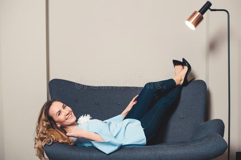 Donna elegante che riposa sullo strato in tacchi alti alla moda delle scarpe Giovane donna di affari che si trova sul sofà grigio fotografie stock