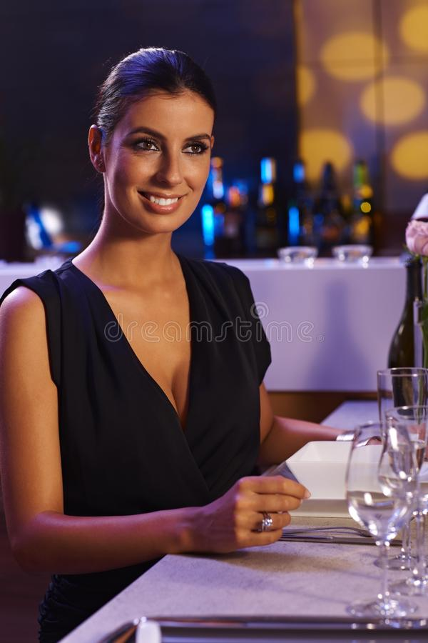 Donna elegante che si siede alla tabella di pranzo immagine stock