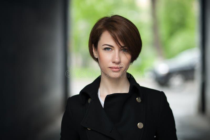 Donna elegante dei bei capelli marroni in rivestimento nero che posa all'aperto immagine stock libera da diritti