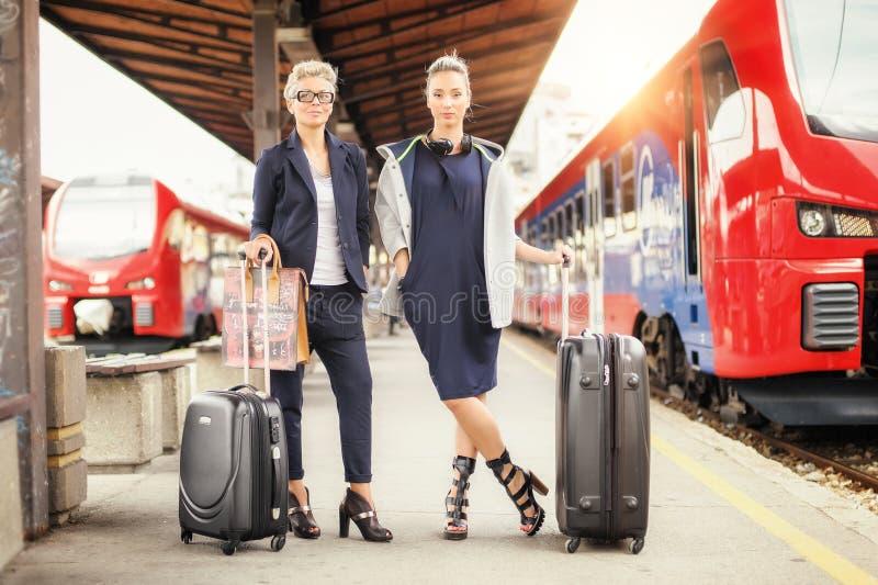 Donna elegante due con la valigia che posa sulla stazione ferroviaria fotografia stock