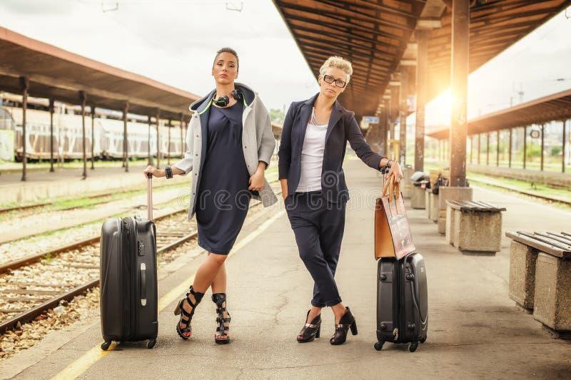 Donna elegante due con la valigia che posa sulla stazione ferroviaria immagini stock libere da diritti