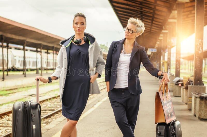Donna elegante due con la valigia che posa sulla stazione ferroviaria immagine stock libera da diritti