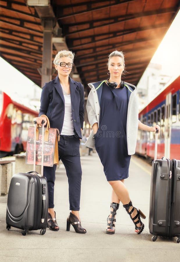 Donna elegante due con la valigia che posa sulla stazione ferroviaria immagine stock
